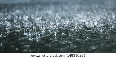 Drops of heavy rain on water - stock photo