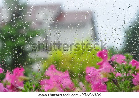 Drops of rain on a window pane, house and garden in background - stock photo