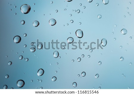 Drops of rain on blue glass - stock photo
