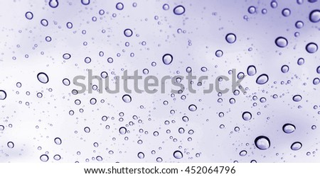 Drops of rain on glass , rain drops on clear window / rain drops with clouds / water drops on glass after rain background / water drops / Small water drops on the glass - stock photo