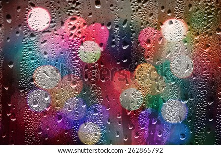 Drops of rain on glass with defocused lights. Abstract blurred background - stock photo