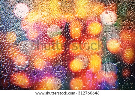 Drops of rain on glass with defocused lights. Abstract colorful blurred background