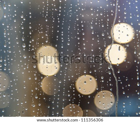 Drops of rain on window with abstract lights - stock photo