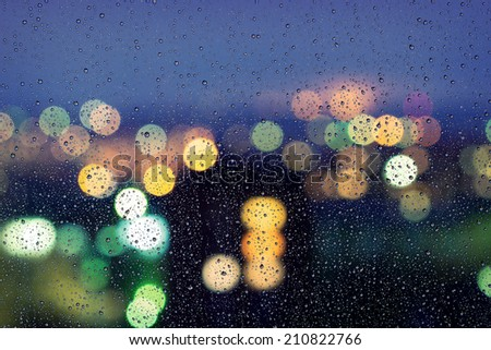 Drops of rain on window with bokeh lights background - stock photo