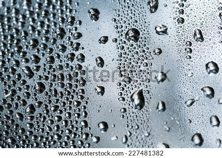 Drops of rain on window with lights background. Color toned image. - stock photo