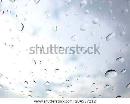 Drops of water on a window with a cloudy sky in the background. - stock photo