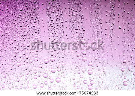 Drops on a glass surface with a pink or red color gradient - stock photo