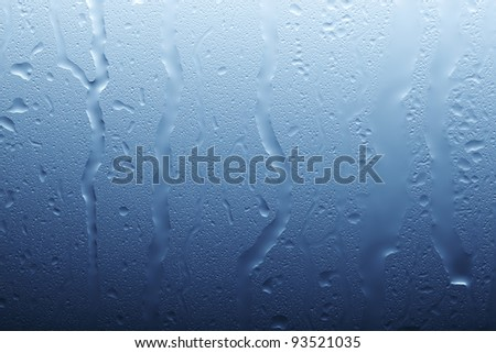 Drops running on a glass surface - stock photo