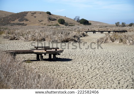Drought conditions in California, dried up lake bed with pier jetty out over the cracked earth with harsh sunlight heating up the landscape, dead grass in the background.  - stock photo