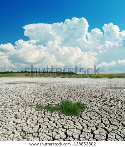 drought earth with green grass under clouds - stock photo
