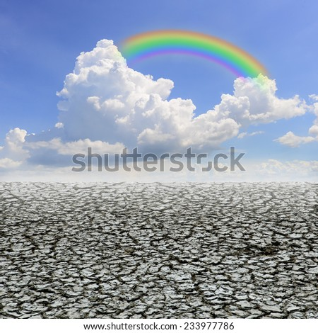 Drought land against a blue sky with clouds and rainbow - stock photo