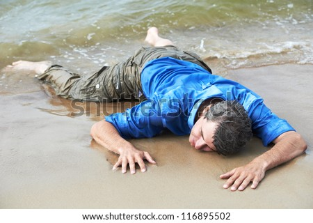 drowned dressed man lying on sea shore at tide - stock photo