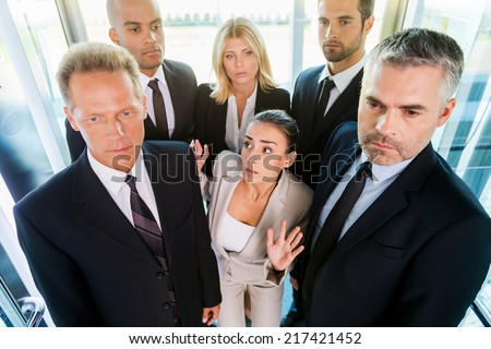 Drowning in people. Top view of fearful young woman in formalwear feeling trapped by the crowd while standing in elevator  - stock photo
