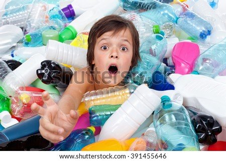 Drowning in the plastic flood - boy reaching out for help from the overflowing garbage - stock photo