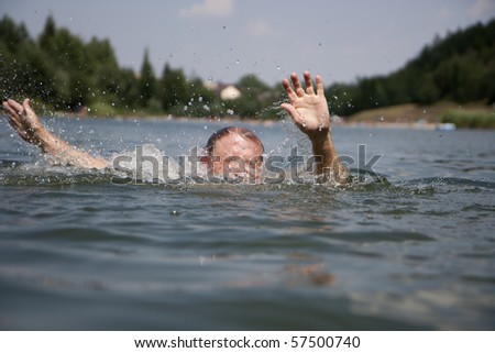 Drowning swimmer at a lake in summer - stock photo