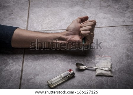 Drug Addict hand with syringe on the floor with a bag of drugs a spoon and a lighter - stock photo