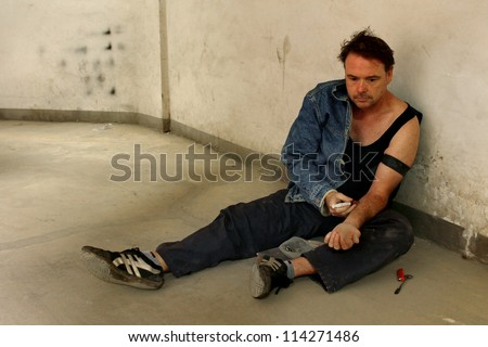 Drug Addict Injecting with a Syringe leaning against a filthy wall