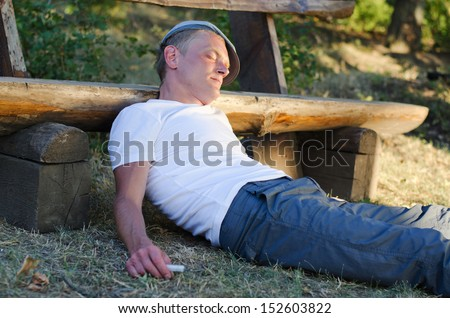 Drug addict with a syringe in his hand lying sprawled on the ground oblivious to his surroundings as he experiences the high of a drug like cocaine - stock photo