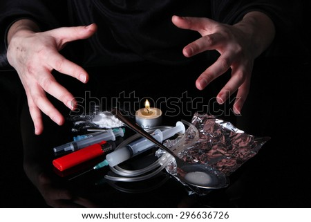 Drug addict with syringe on black background - stock photo