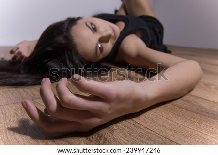 Drug addict woman sleeping on wooden floor. closeup shot of female hand lying drugged and doped - stock photo