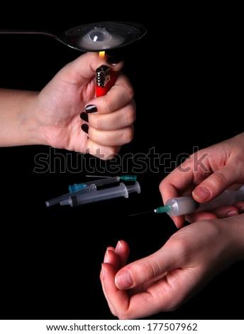 Drug addicts with syringe on black background - stock photo