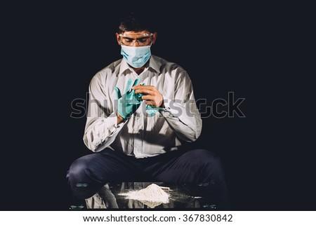 Drug dealer with gloves preparing cocaine - stock photo