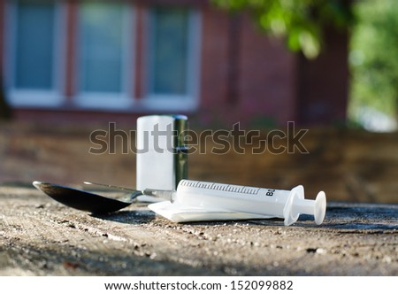 Drug paraphernalia for the preparation and injection of cocaine with a spoon and lighter for heating the powder and syringe for an addict to inject it - stock photo