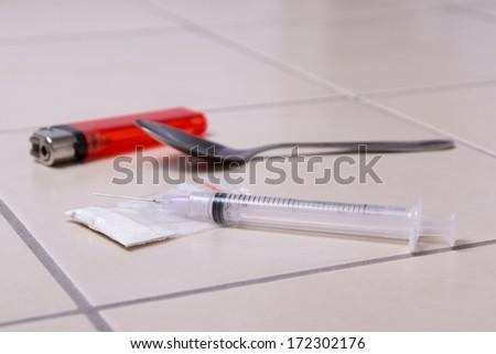 drug syringe, heroin powder, spoon and lighter on tiled floor - stock photo