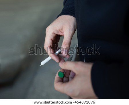 drug use, substance abuse, addiction, people and smoking concept - close up of addict hands with marijuana joint and blunt tube on street - stock photo