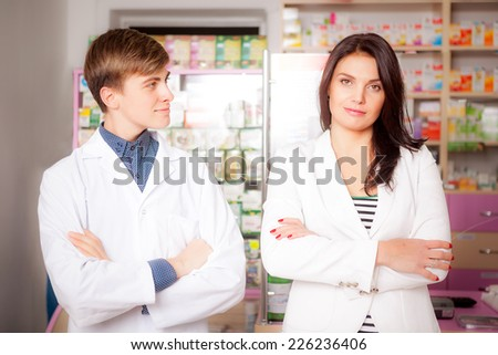 Druggist and client in front of pharmacy table. Drugs and pills in the background. Medical background