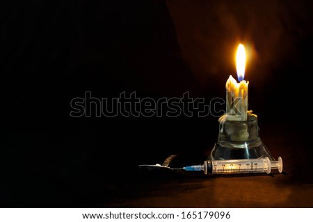 Drugs abuse and addiction concept. Candle, syringe and spoon isolated black background. - stock photo