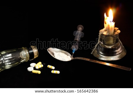 Drugs abuse and addiction concept. Candle, syringe, pill, liquor bottle and spoon isolated black background. - stock photo