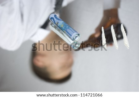 Drugs and money on a mirror. Out of focus reflection of addicted businessman. - stock photo