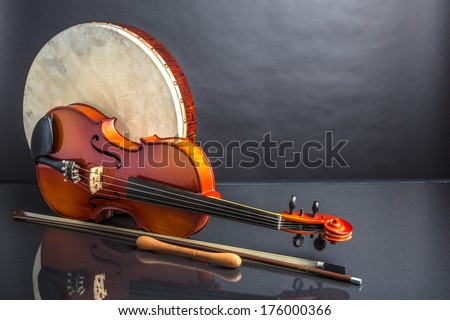 Drum and Fiddle. A Irish drum  (bodhran) and a viola on a black background - stock photo