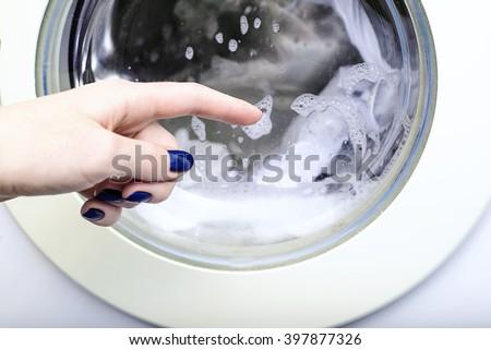 Drum washing machine, things in the washing machine, the hand points to erasing the washing machine drum - stock photo