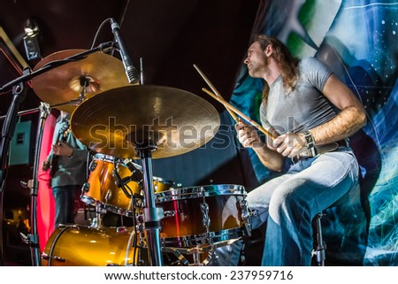 Drummer (focus on the drum and microphone) playing on drum set on stage. Warning - authentic shooting with high iso in challenging lighting conditions. A little bit grain and blurred motion effects. - stock photo