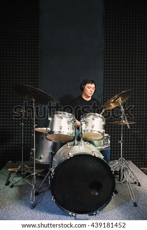 Drummer in headphones playing solo on drum set. Front view on male drummer playing sound composition on drums at sound recording studio. - stock photo