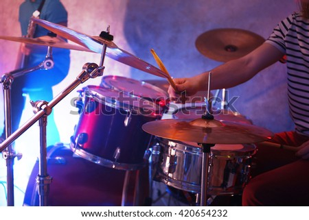 Drummer playing on drum set on stage. - stock photo