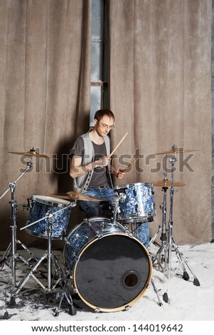 Drummer plays drums in room powdered with snow - stock photo