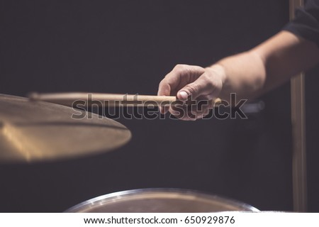 Drummer plays with drumstick