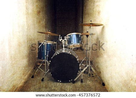 Drums conceptual image. Drum set percussion and cymbals in the dark corridor. Retro vintage grunge picture. - stock photo