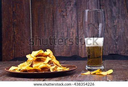 drunk a glass of beer on the table with chips - stock photo