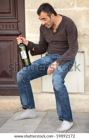drunk alcoholic man standing near house entrance in the city - stock photo