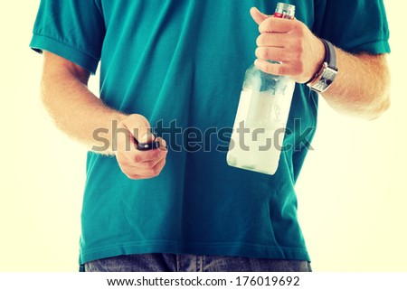 Drunk driver concept - young man with vodka and car keys - stock photo