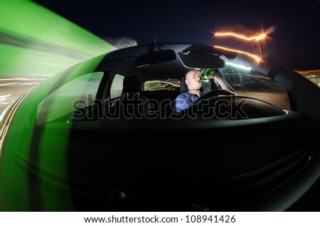 Drunk driver drinking beer while driving a car at night - stock photo