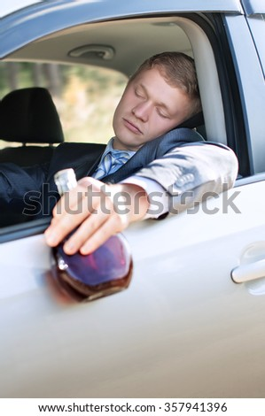 Drunk driver fell asleep at the wheel of a car with a bottle - stock photo