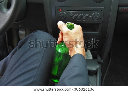 Drunk driver with green bottle - stock photo