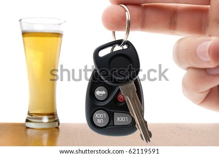 Drunk driving conceptual image with a hand holding some car keys and a glass of beer in the background.  Shallow depth of field. - stock photo