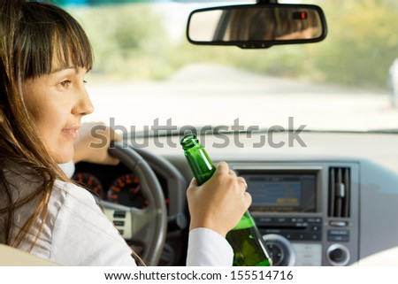 Drunk female driver drinking alcohol from the bottle turning and talking to a passenger while driving down a road losing all concentration - stock photo