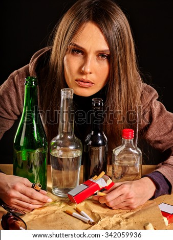 Drunk girl covers group bottles of alcohol. Soccial issue alcoholism. - stock photo